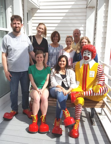 Eight Hawkes employees sit and stand next to the Ronald McDonald statue and try to avoid his unwavering gaze.